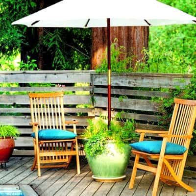 Creating Whimsy In Your Backyard & Garden, Part Two. A patio umbrella holder/planter in a shady reading area for outdoor living