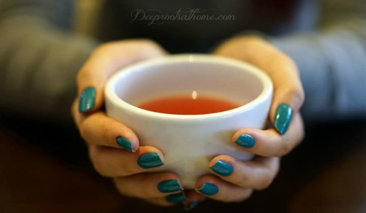 10 Tried & True Reasons Raspberry Leaf Is Great For All Women. A woman holding a cup of red raspberry tea.