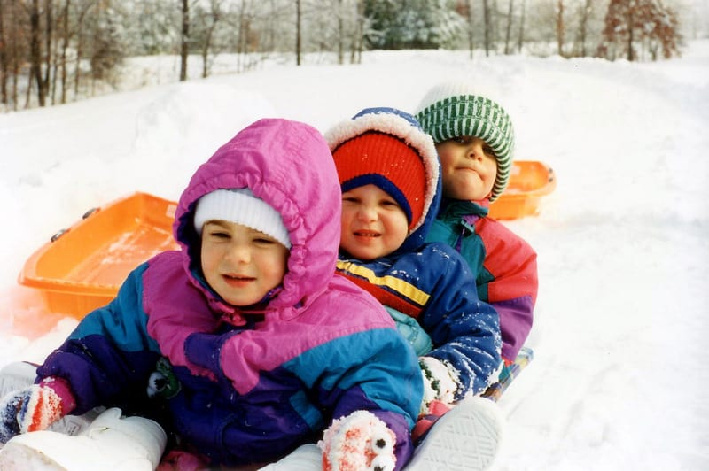 Using Color In Winter, To Cheer The Home & Heart. children on sled in bright snow bibs, snowy day play