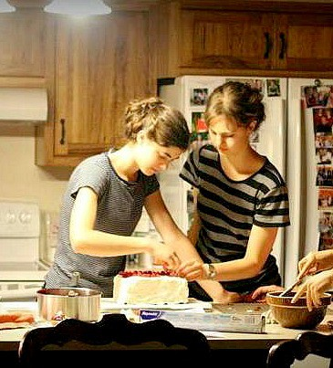 2 friends frosting a cake and baking together.
