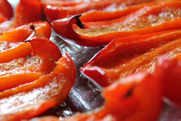Red peppers roasting on the grill.