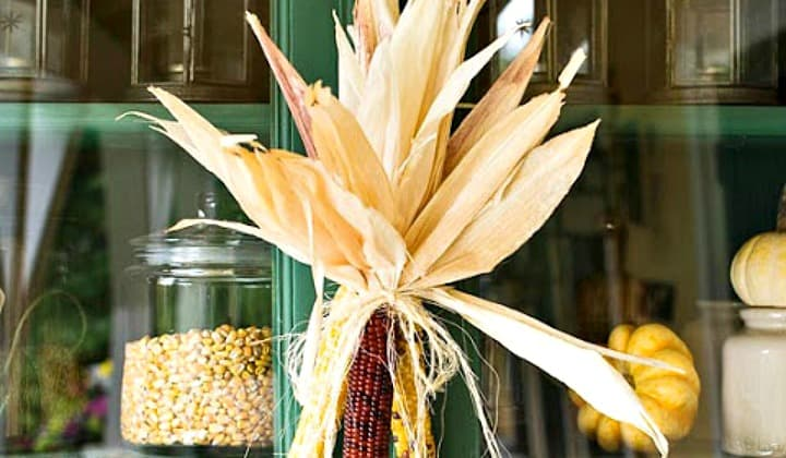 18 Classy, Natural Elements for Fabulous Fall Decor & Color. A green rustic kitchen cupboard with an Indian corn cob hung on front