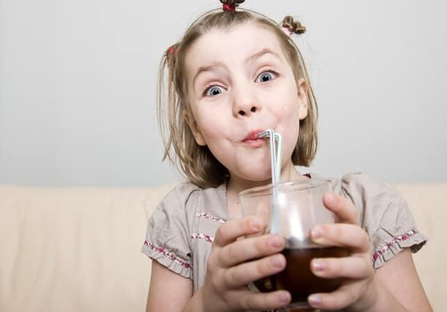 How Could A Diet Soda A Day Be A Problem? Here Are 8 Ways. A 10 year old drinking a carbonated soda with a straw.
