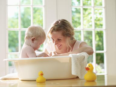 A baby taking a restful bath in a bathtub with a cheerful mother right beside