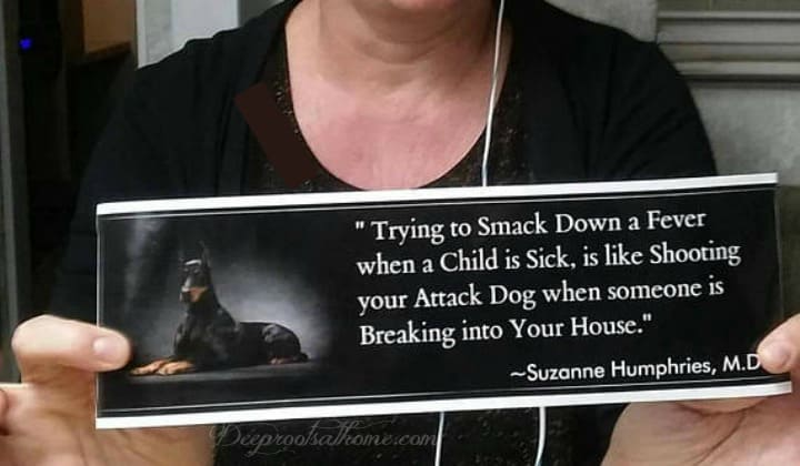 Knocking Down A Fever Is Like Shooting Your Attack Dog In a Burglary. Dr. Suzanne Humphries holding her 'Smack down a fever is like shooting your attack dog' quote.