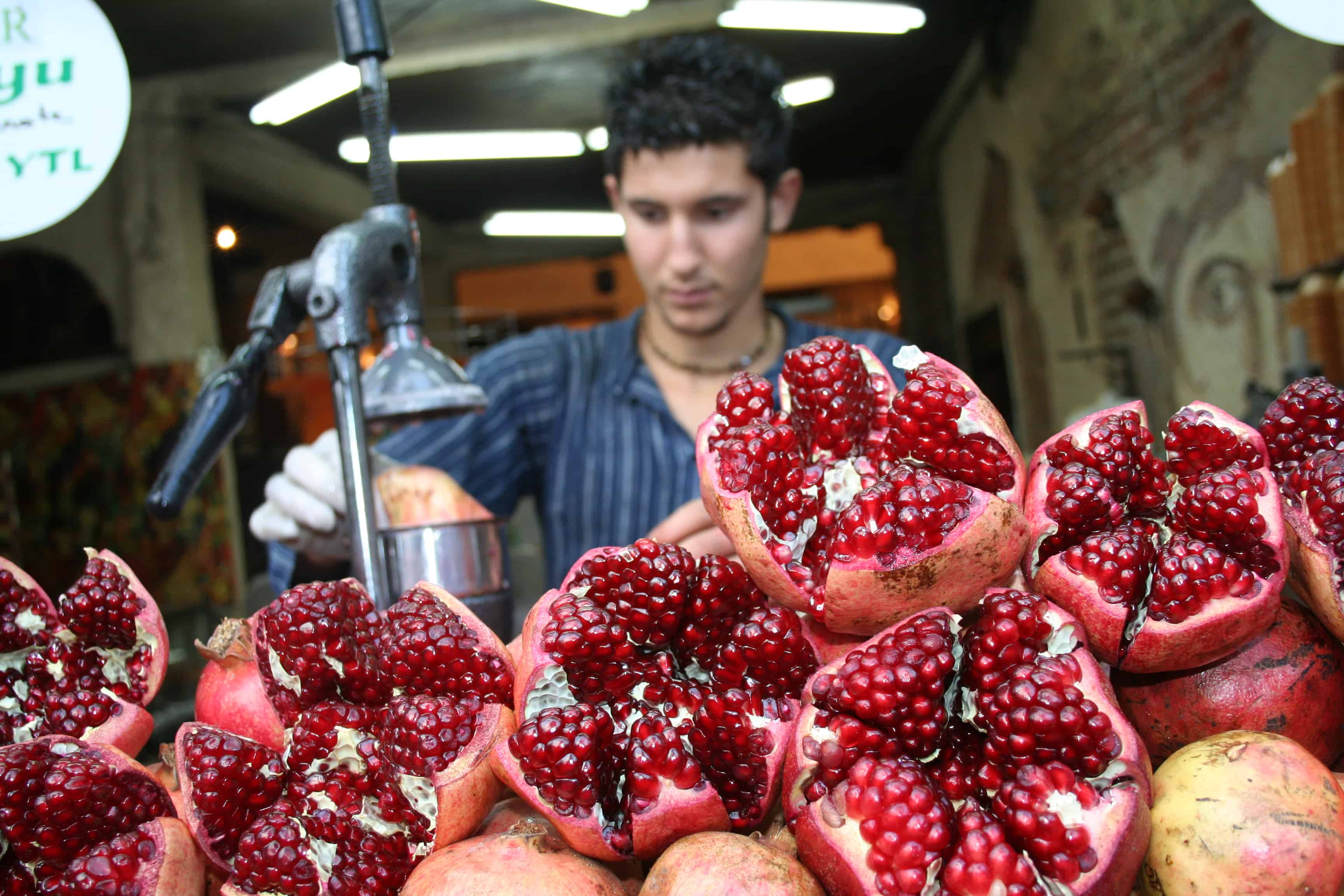 Research: Pomegranate Juice Reverses Heart Blockage. Man opening up pomegranates