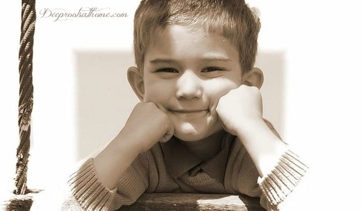 Boys Think, See, Hear & Process Very Differently Than Girls. A cute smiling 7-8 year old boy with his chin resting on hands.