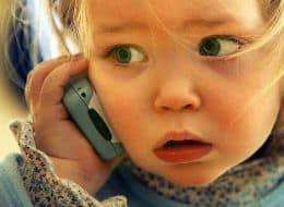 a small child holding cell phone to ear