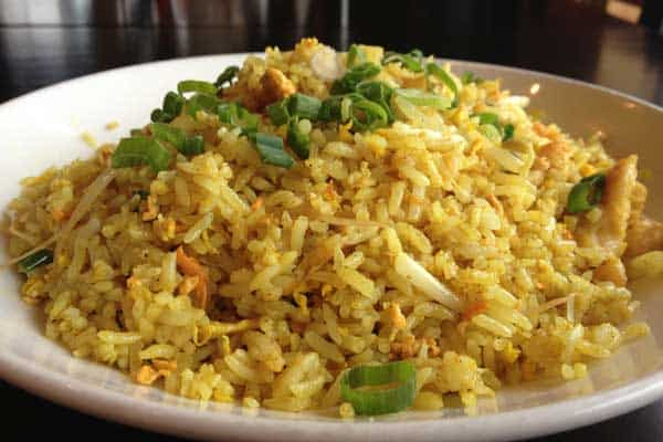 How To Make {& Use} Highly Bioavailable Turmeric Golden Paste, turmeric fried rice with golden paste added on a plate with green onions