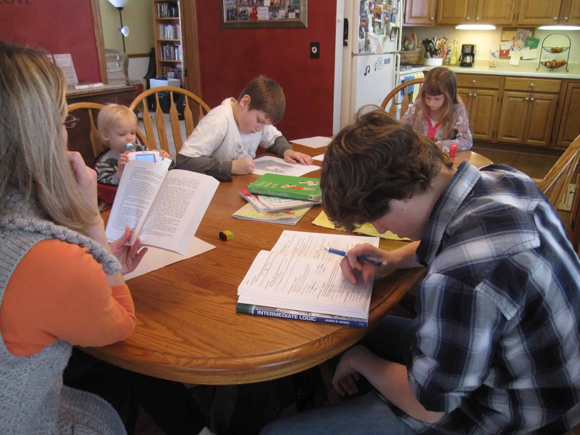 students sitting around the dining room table working on their classes. Mom is reading.