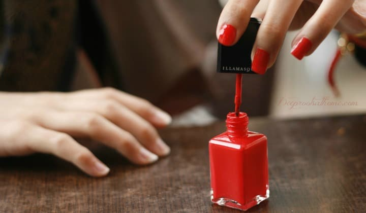 9 Less-Toxic & Non-Toxic Nail Polish Brands. Woman polishing her fingernails red.