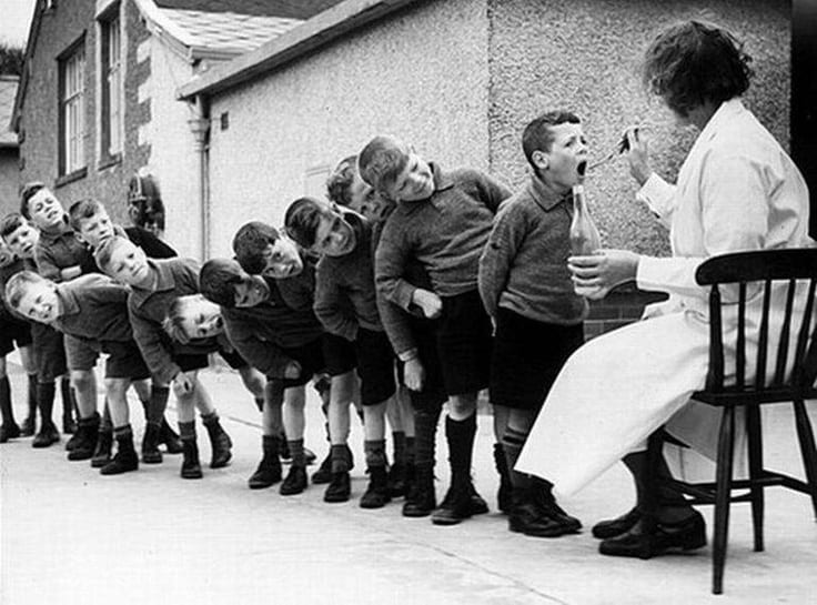 Old photo of young children at a school in Europe lined up, takingCLO on spoon,