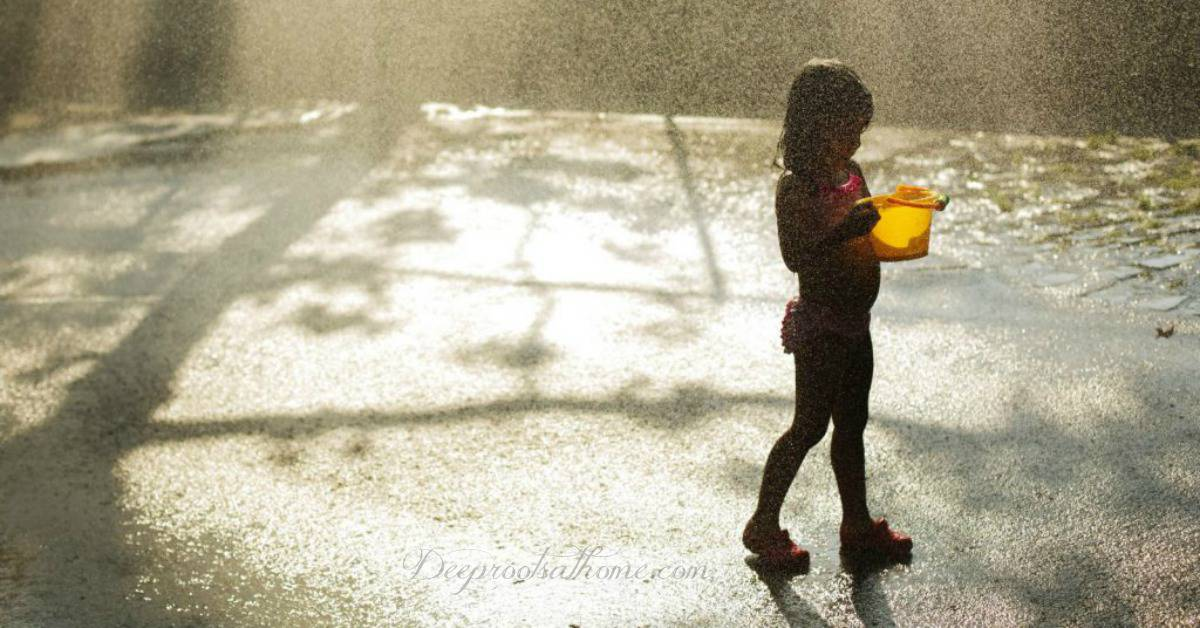It's Not Dangerous For Kids To Be Bored Sometimes. Young child in a swimsuit entertained with only the rain and a bucket
