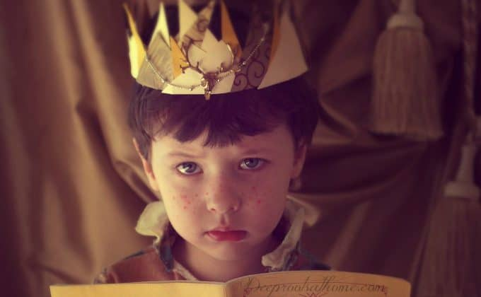 a little boy with a crown on his head - a symbol of all bored kids