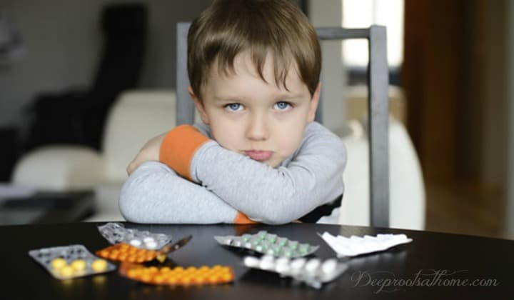 8M US Kids Taking Psychiatric Drugs: Parents Not Told The Deadly Documented Risks. A pouting boy at a table with colorful psychiatric drugs in their packages spread out before him.