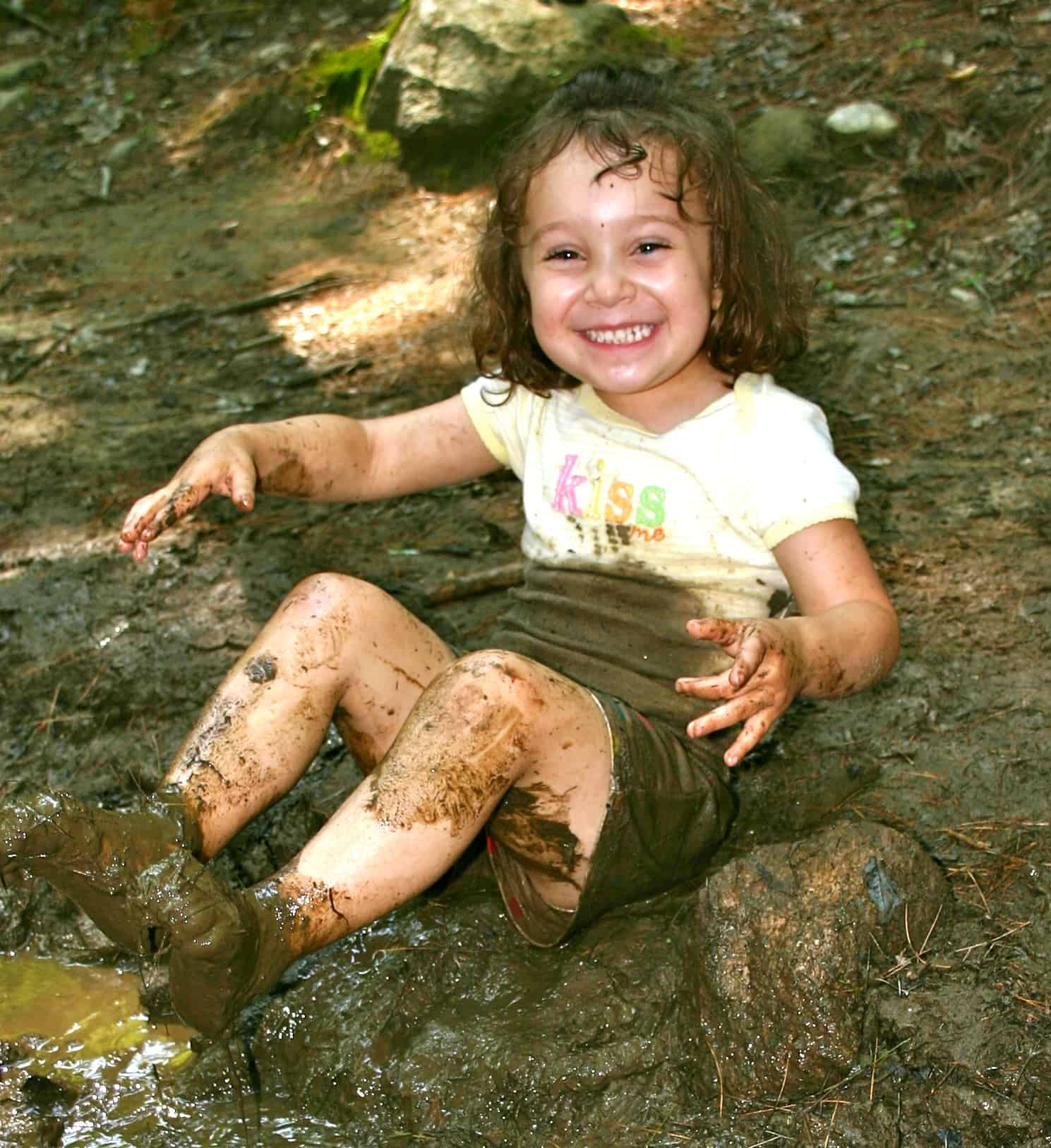 happy little girl playing hard at the edge of a creek