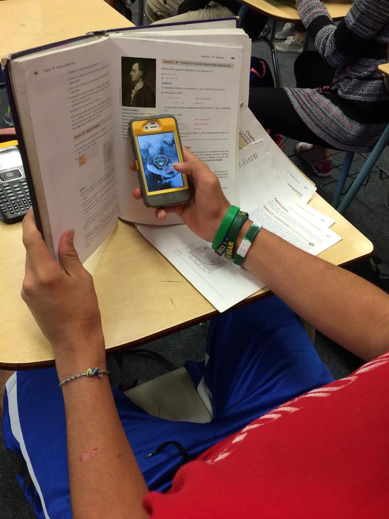 7 Truths Parents & Adults Don't Get About Today's High School. A student hiding his game on the iPhone behind his school book.