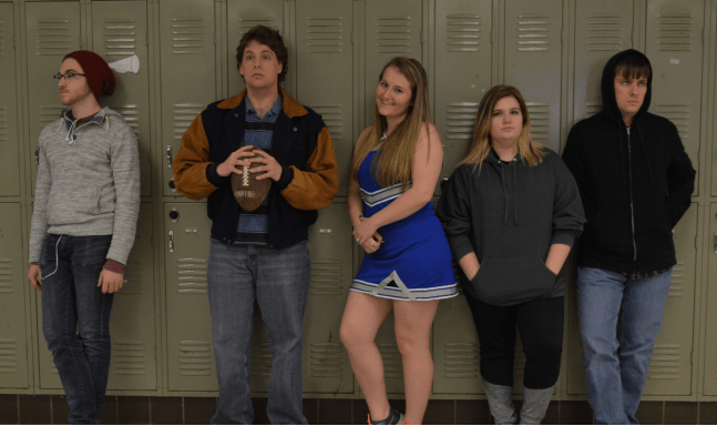 7 Truths Parents & Adults Don't Get About Today's High School. 5 kids standing by their lockers in a high school...looking bored. one is a cheerleader in uniform.
