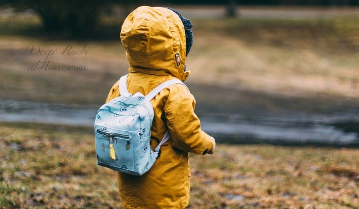 9 Unexpected Things Learned In Healing My Child from ADHD & Anxiety. A young child in a yellow parka with a little backpack on his back walking towards a river.
