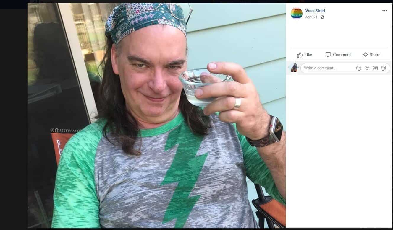 A man in a green shirt toasting himself