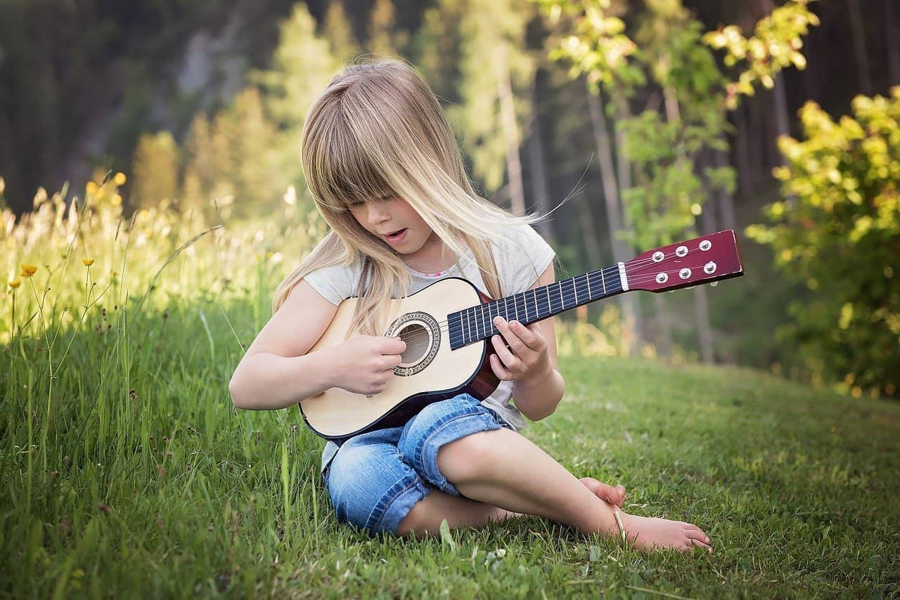 25 Foundational Hymns To Teach Your Children While Young. girl with ukulele